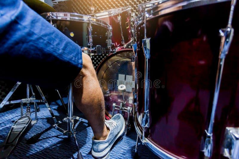 De mens zette witte sportschoenen en spelend het drumstel en de baarzen trommel met voet in muziekruimte royalty-vrije stock fotografie
