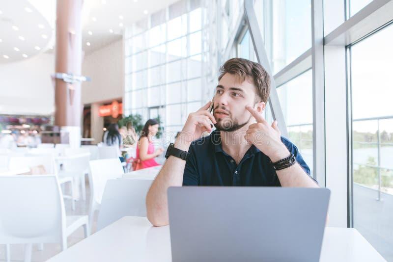 De mens zit bij een restaurant dichtbij het venster, werkt aan laptop, spreekt op de telefoon en kijkt weg stock fotografie