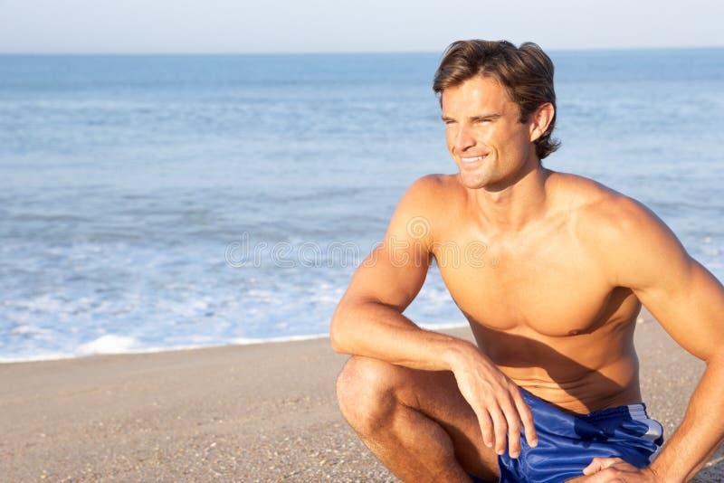De mens zit bij strand het ontspannen royalty-vrije stock foto