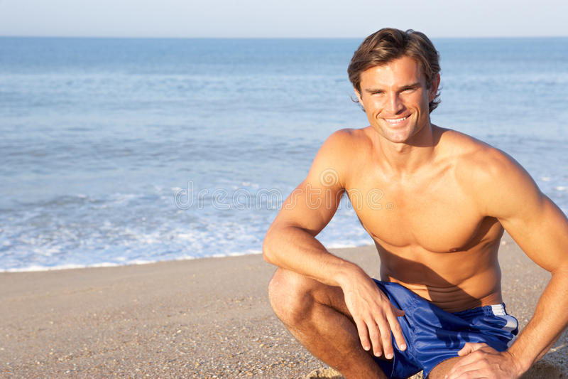 De mens zit bij strand het ontspannen stock fotografie