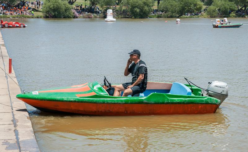 de mens zit in boot en het spreken op zijn mobiele telefoon stock afbeeldingen