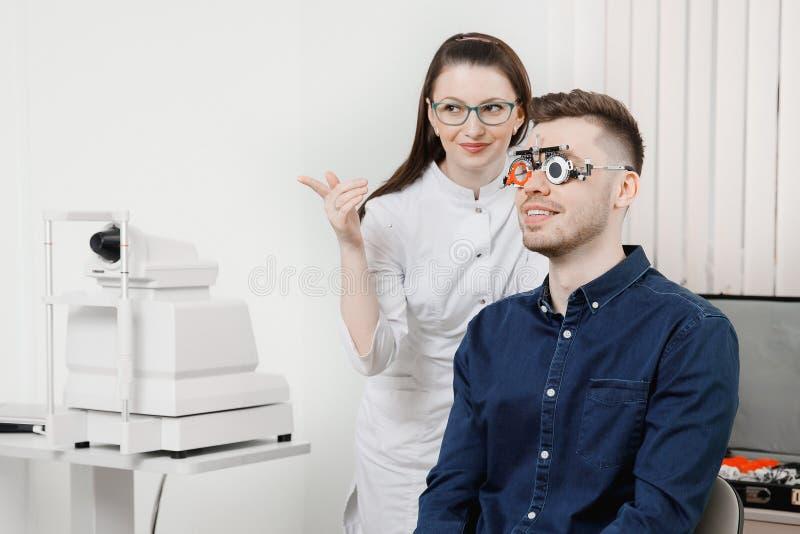 De mens zit en glimlacht in een ijzerkader voor selectie van de oftalmoloog van de de ogenontvangst van glazenlenzen royalty-vrije stock afbeeldingen