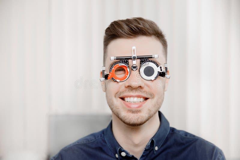 De mens zit en glimlacht in een ijzerkader voor selectie van de oftalmoloog van de de ogenontvangst van glazenlenzen stock fotografie