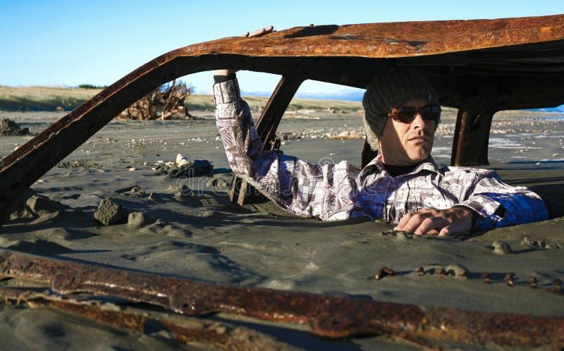 De mens zit in geroest die autowrak in zand op strand wordt begraven royalty-vrije stock afbeeldingen
