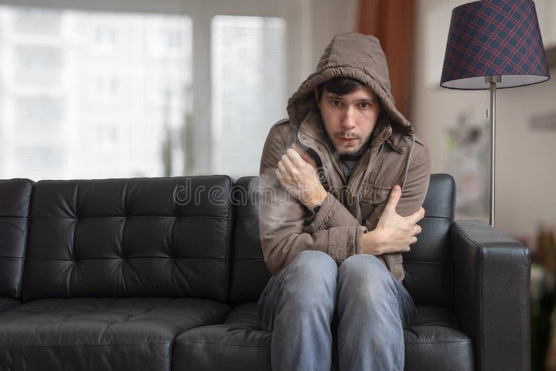 De mens zit op bank thuis en voelt koud stock foto's