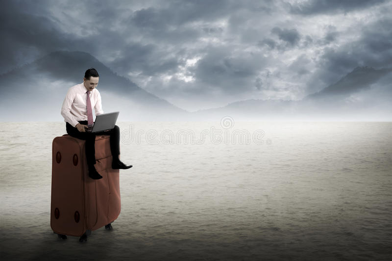 De mens zit op de koffer, die met laptop bij de woestijn werken royalty-vrije stock foto