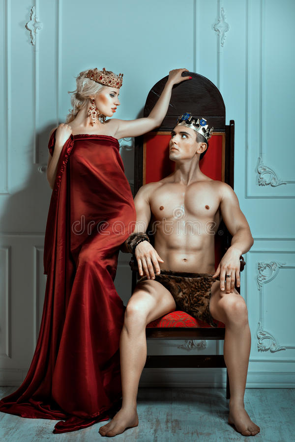 De mens zit op de troon en bekijkt koningin stock fotografie