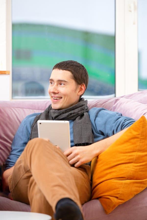 De mens zit op de laag en het gebruiken van een tabletcomputer stock afbeeldingen