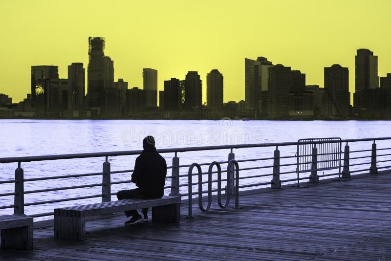 De mens zit op parkbank lettend op de zonsondergang over Hudson River in de Stad van New York stock foto's