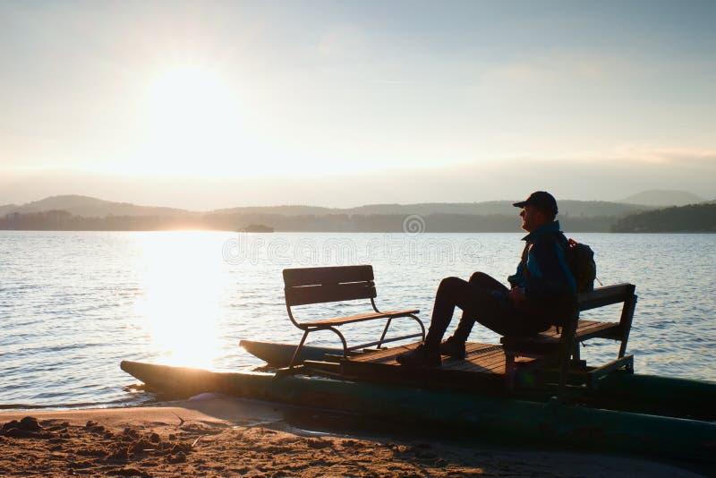 De mens zit op verlaten oude roestige die pedaalboot op zand van strand wordt geplakt Golvende waterspiegel, eiland op horizon stock fotografie