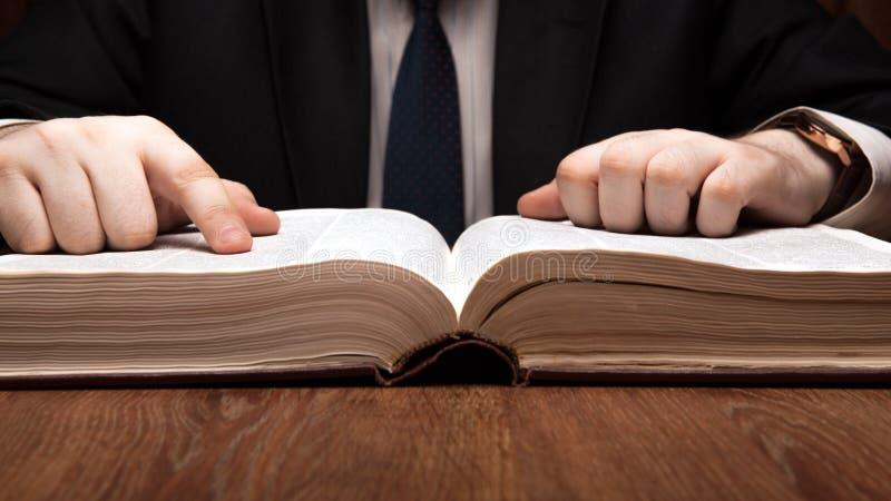 De mens zoekt informatie in het woordenboek royalty-vrije stock foto's