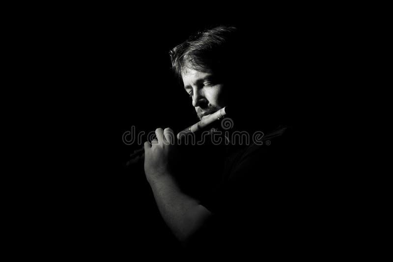 De mens in zwarte speelt een fluit royalty-vrije stock foto