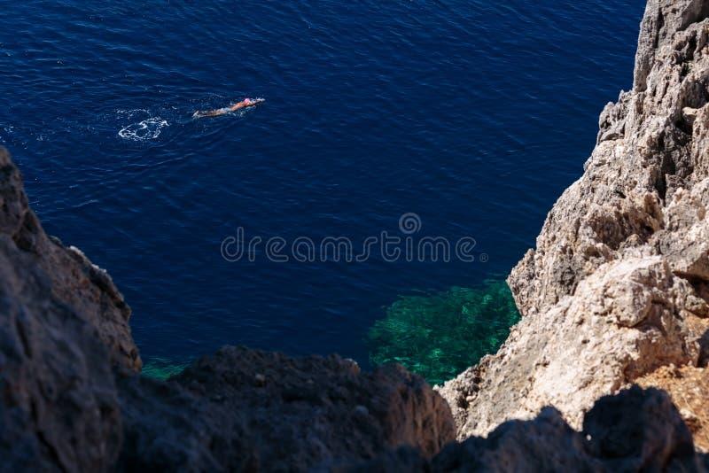 De mens zwemt in het donkerblauwe overzees stock afbeelding