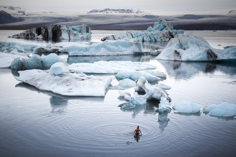 De mens zwemt in koud water Ontzagwekkende mening over het gletsjerverstand royalty-vrije stock foto's