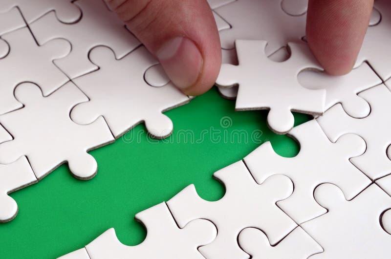 De menselijke hand baant de weg aan de oppervlakte van de puzzel, die een groene ruimte vormen Het concept het overwinnen van dif royalty-vrije stock afbeeldingen