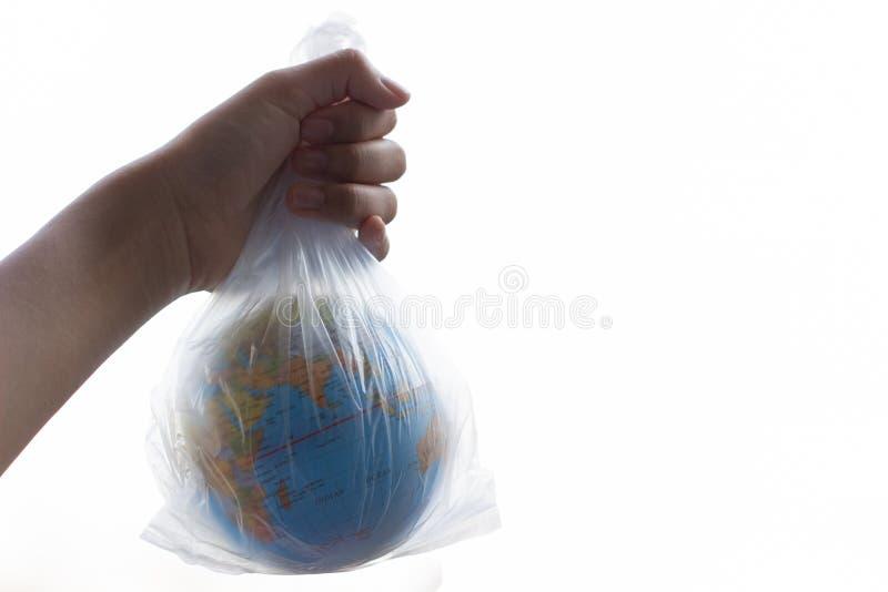 De menselijke hand houdt de aarde in een plastic zak stock afbeeldingen