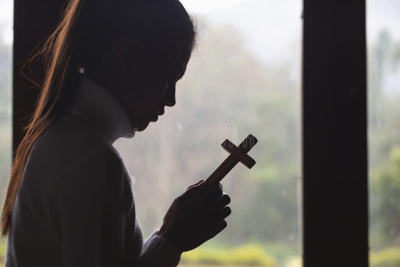 De menselijke hand houdt dwars gebedconcept voor geloof, spiritualiteit en godsdienst Christelijk concept stock fotografie