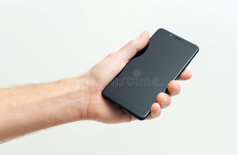 De menselijke hand houdt een zwarte smartphone stock fotografie