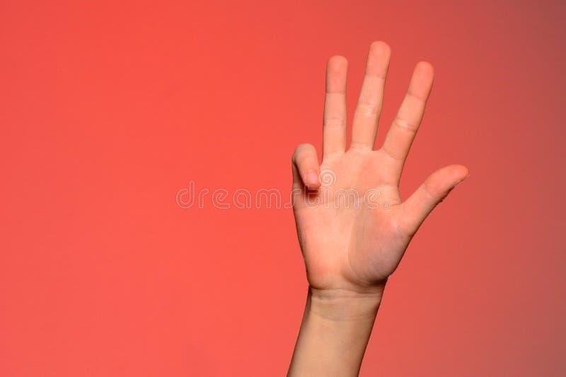 De menselijke hand toont vier vingers die op een rode achtergrond worden geïsoleerd stock afbeelding