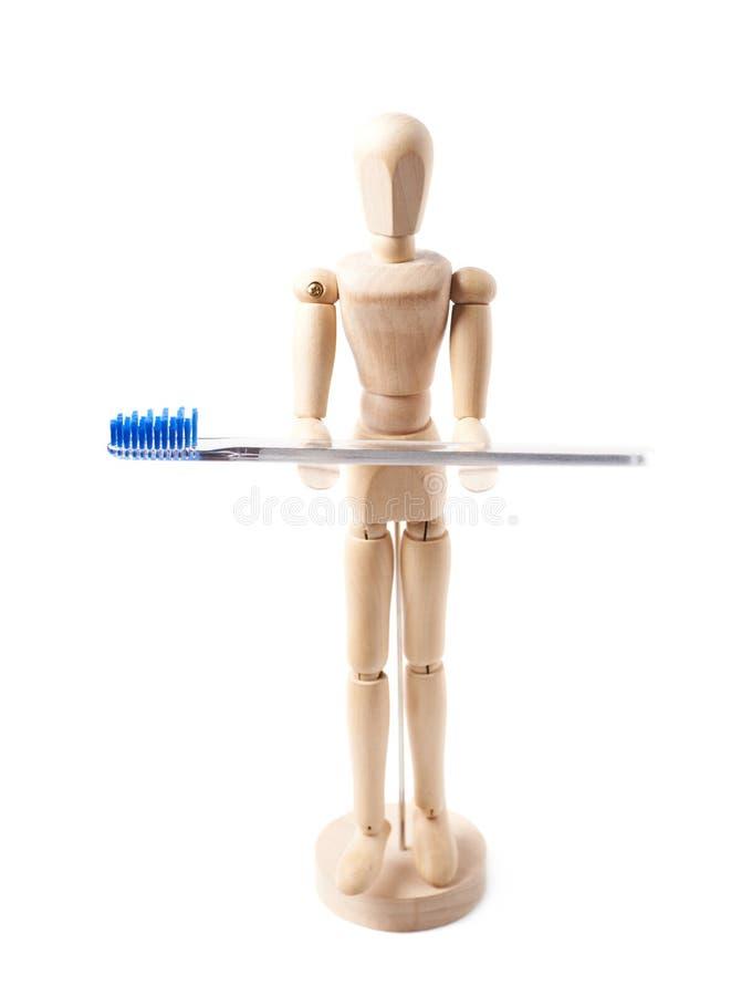 De menselijke houten tandenborstel van de poppenholding stock afbeelding