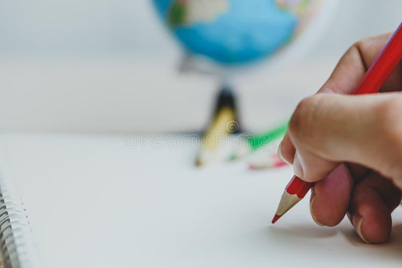De menselijke kleurpotloden die van het handgebruik iets trekken op Witboek stock foto's