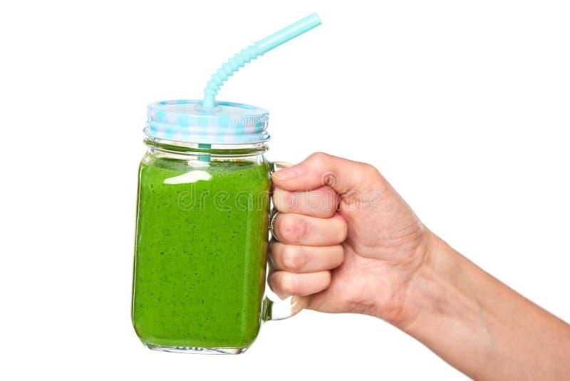 De menselijke mok van de de kruiktuimelschakelaar van de handholding met groene smoothie stock afbeelding