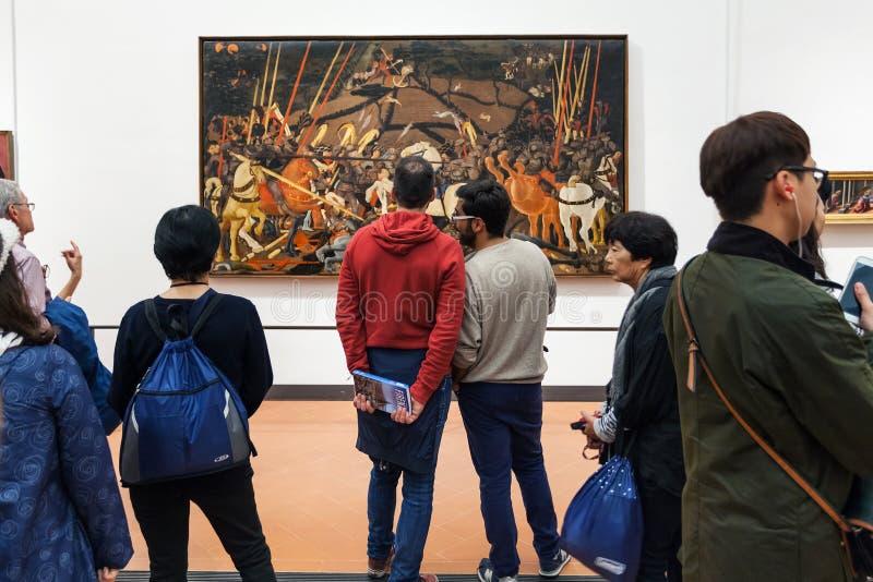 De mensen bekijken het schilderen in ruimte van Uffizi-Galerij stock fotografie