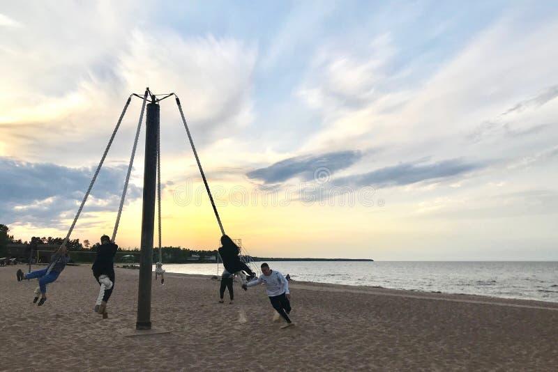 De mensen berijden de carrousel op een zandig strand royalty-vrije stock fotografie