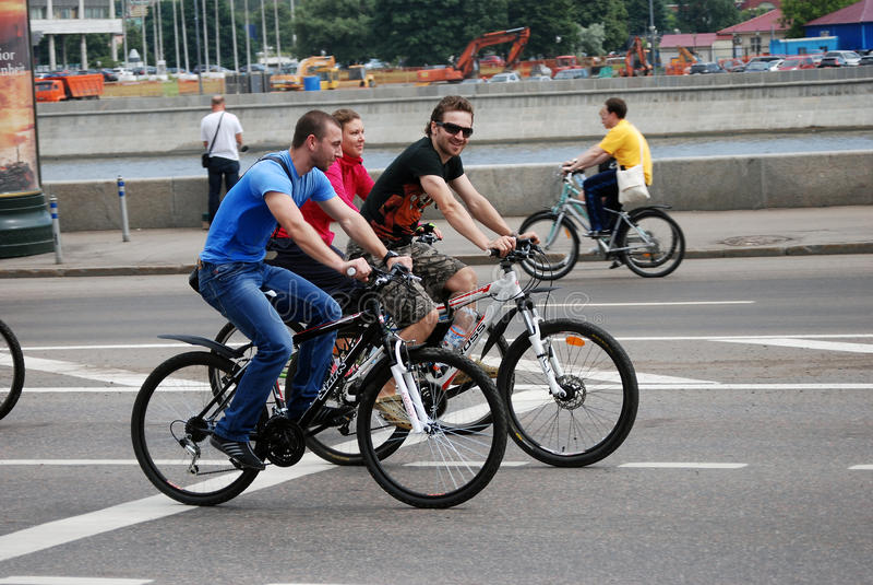 De mensen berijden fietsen in Moskou Één mens bekijkt camera en glimlacht stock foto's