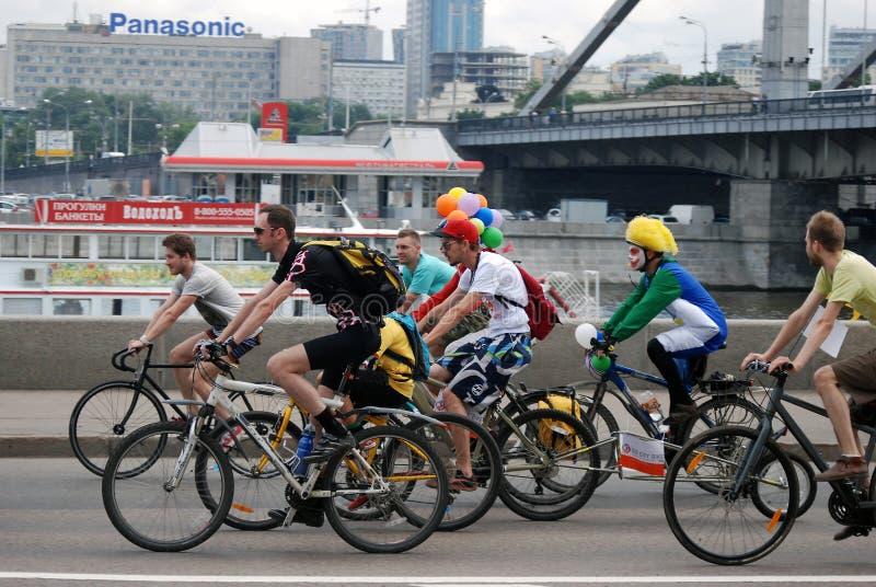 De mensen berijden fietsen in Moskou Er zijn clowns onder hen royalty-vrije stock foto's