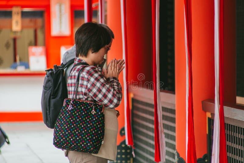 De mensen betalen hulde werpen muntstukken en schudden de klok aan heilige zegen in het Japanse heiligdom stock foto