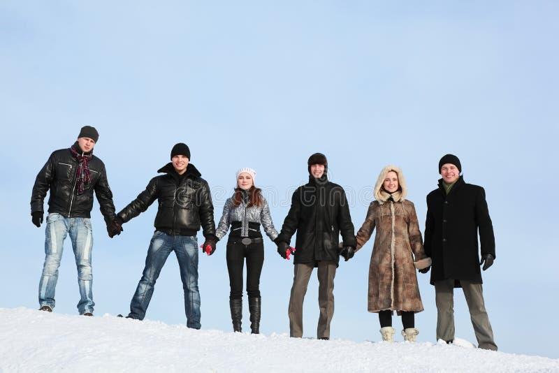 De mensen bevinden zich op sneeuw en om op handen te houden royalty-vrije stock fotografie