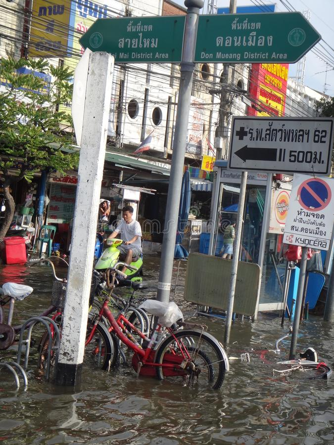 De mensen bieden het hoofd aan het water in een overstroomde straat in Rangsit, Thailand, in Oktober 2011 stock afbeeldingen