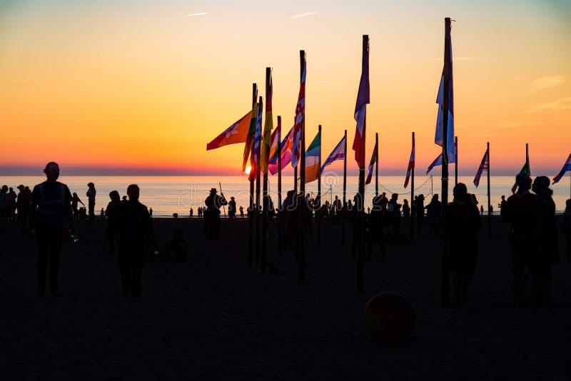 De mensen bij het strand van verschillende landen met daar markeren royalty-vrije stock fotografie