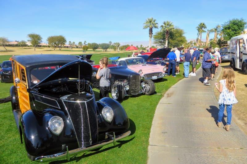De mensen bij liefdadigheidsauto tonen het bewonderen rijen van klassieke, hete staaf en speciale die renteauto's bij een golfcur royalty-vrije stock afbeeldingen