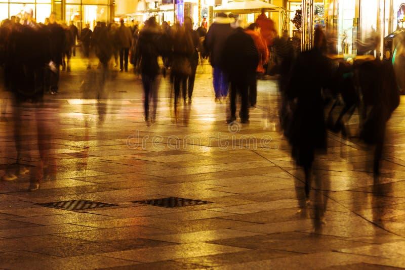 De mensen die in een het winkelen straat in motie lopen vertroebelen bij nacht stock foto's