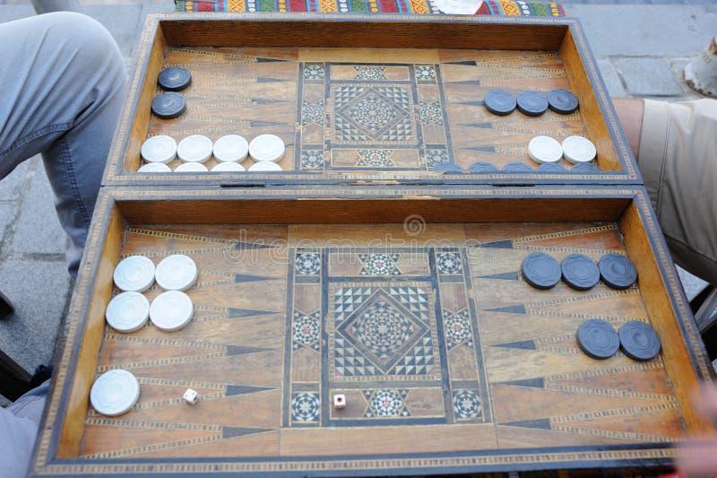 De mensen die het spel van de backgammonraad met een oude houten lijst spelen, controleurs en dobbelen in Turkije stock foto
