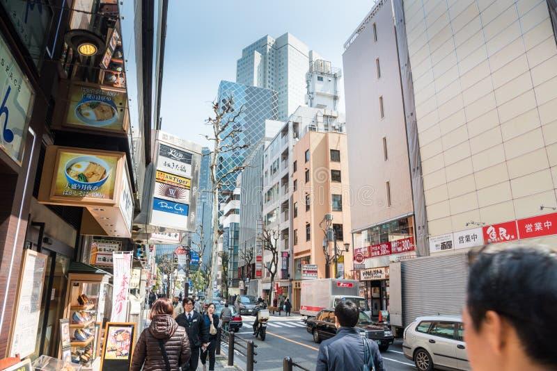 De mensen die langs een Straat wandelen voerden met restaurants en winkels in Centraal Tokyo royalty-vrije stock fotografie