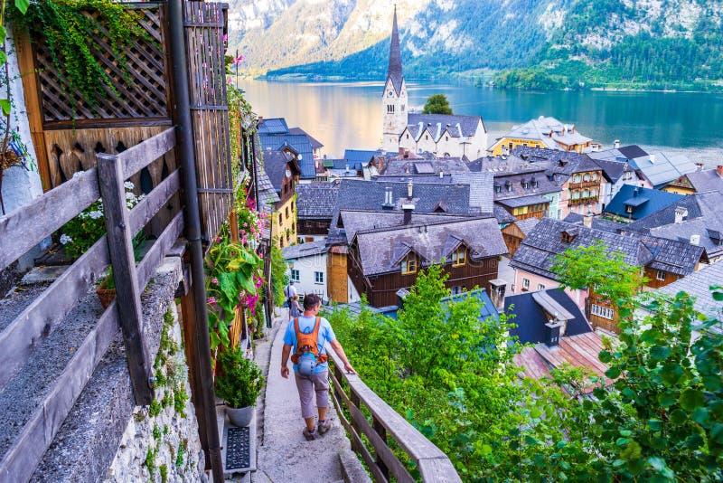 De mensen die neer op smalle oude treden boven Hallstatt, met adembenemende meningen van Meer Hallstatt Hallstatter lopen zien stock fotografie