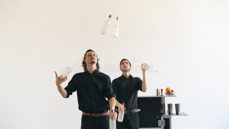 De mensen die van de Professinalbarman met flessen binnen jongleren en cocktail schudden bij mobiele barlijst aangaande witte stu stock foto's