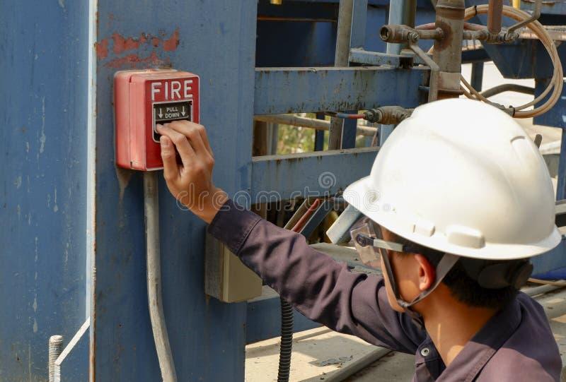 De mensen die veiligheidshelmen dragen drukken brandalarmen stock foto's