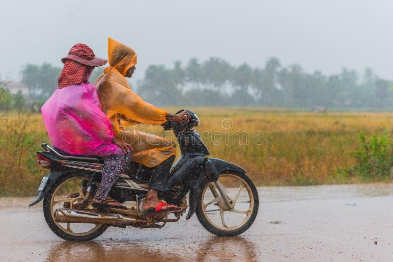 De mensen dragen packable regenjassen terwijl rit een autoped royalty-vrije stock foto's