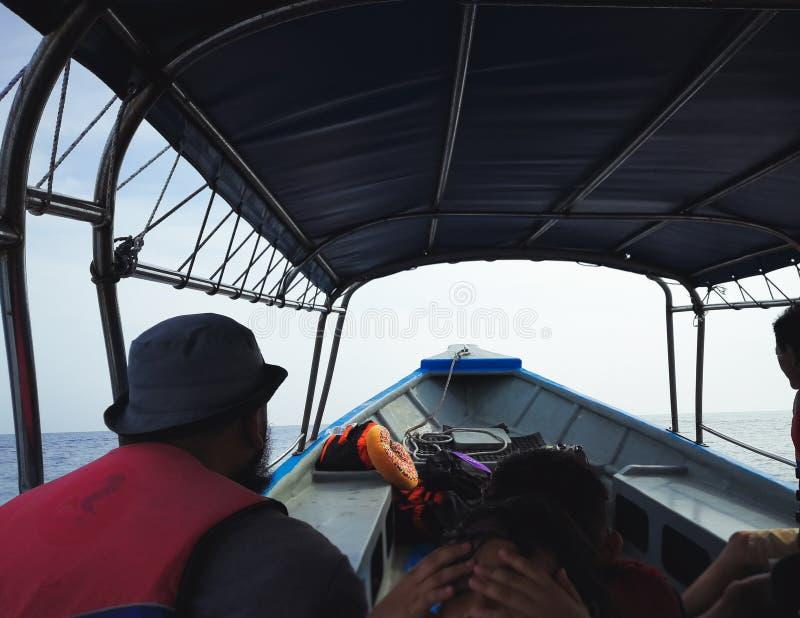 De mensen in een motorboot halen aan een tropisch eiland over royalty-vrije stock afbeeldingen