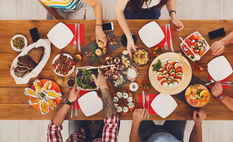 De mensen eten gezonde maaltijd bij de feestelijke partij van het lijstdiner stock foto's