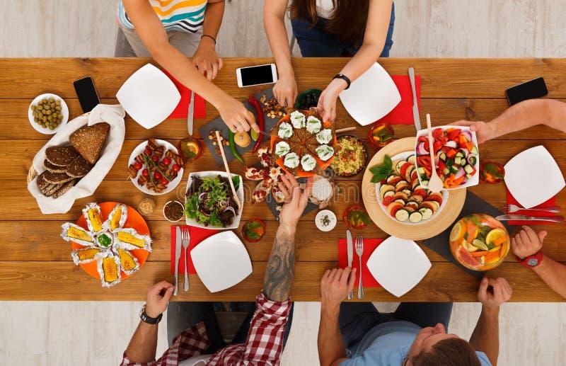 De mensen eten gezonde maaltijd bij de gediende partij van het lijstdiner royalty-vrije stock fotografie
