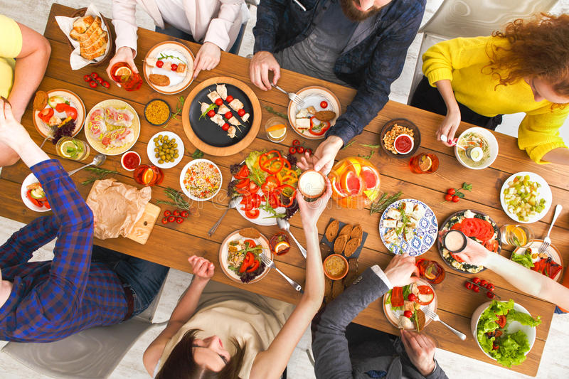 De mensen eten gezonde maaltijd bij de gediende partij van het lijstdiner royalty-vrije stock afbeeldingen