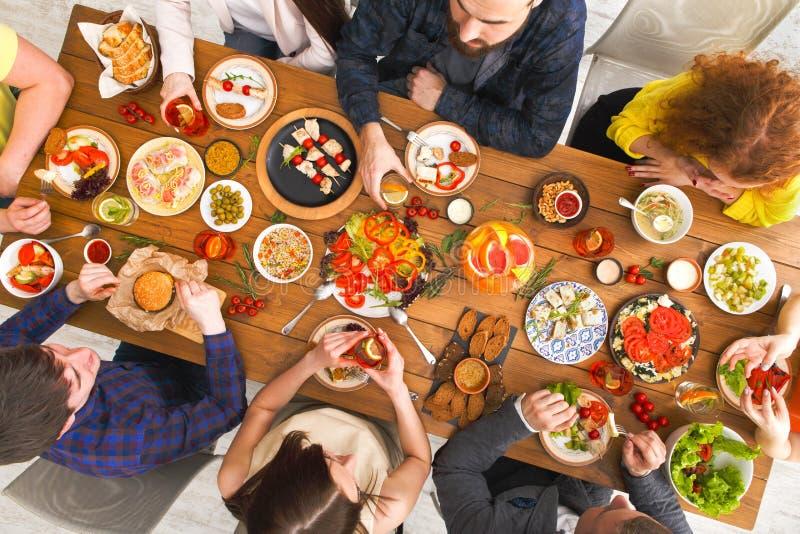 De mensen eten gezonde maaltijd bij de gediende partij van het lijstdiner stock afbeelding