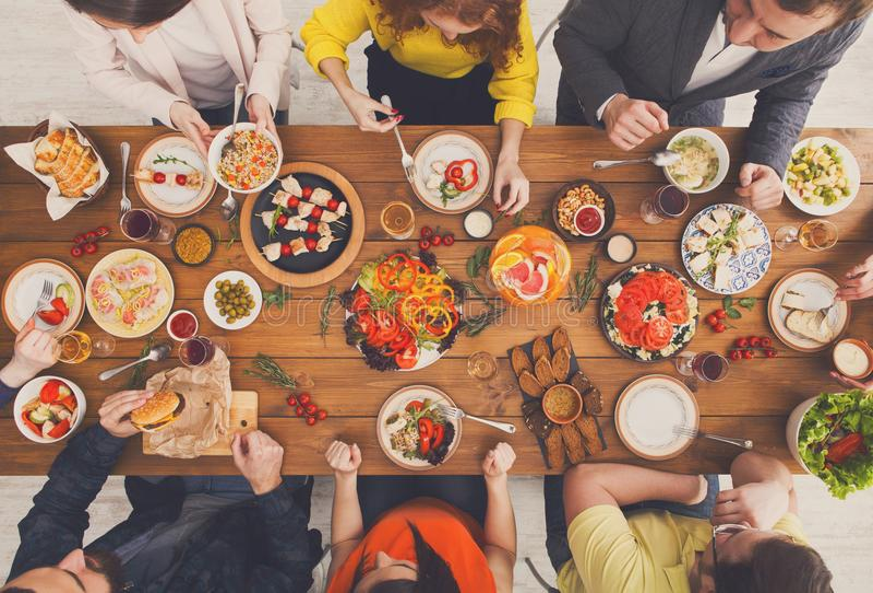 De mensen eten gezonde maaltijd bij de gediende partij van het lijstdiner stock afbeeldingen