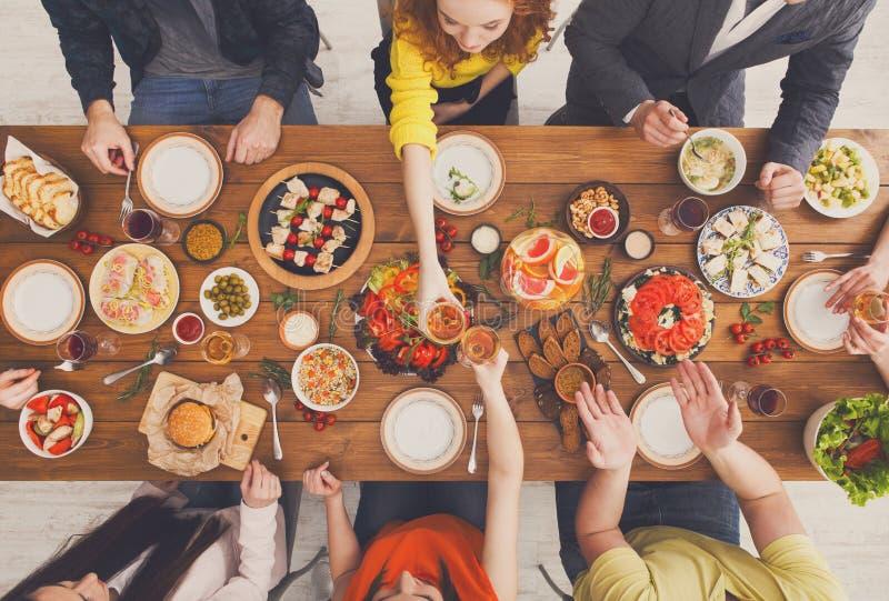 De mensen eten gezonde maaltijd en gerinkelglazen bij de gediende partij van het lijstdiner stock foto's