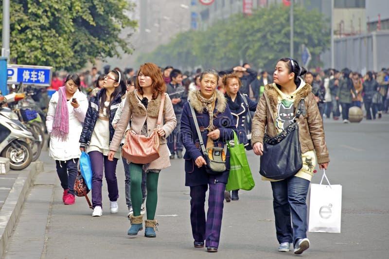 De mensen gaan door een het winkelen straat over stock afbeeldingen